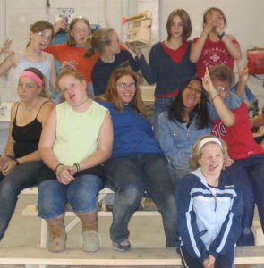 Campers make silly faces on a bench they built at Rosies Girls in 2005