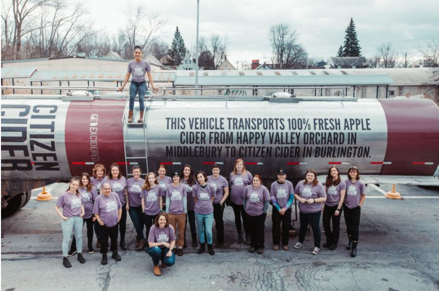 Women who work at Citizen Cider pose for a photo in front of the company's beverage truck.