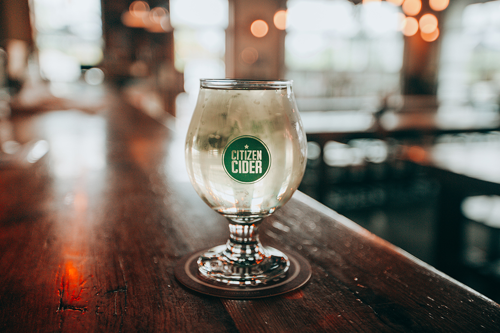 A glass of Citizen Cider on top of a bar.