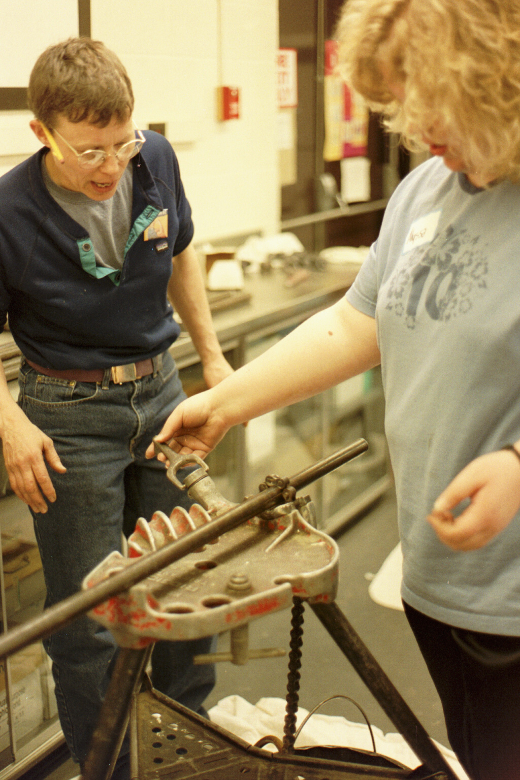 Instructor looks on as participant uses tool